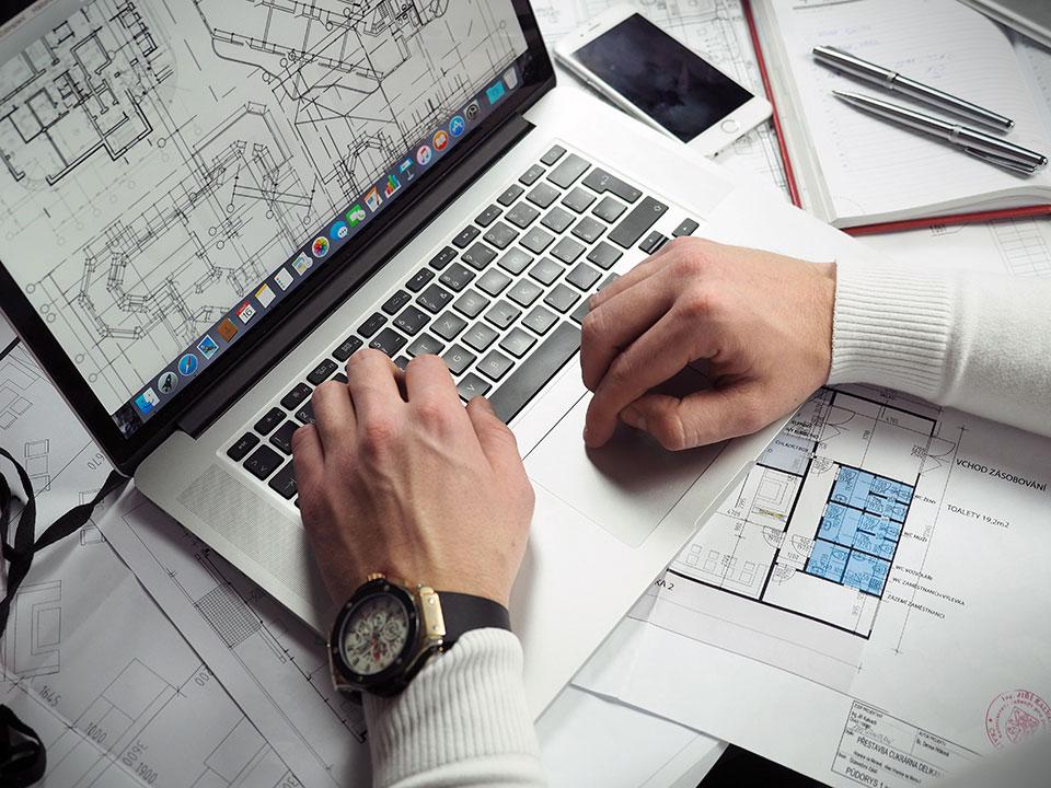 Händer och en dator med en ritning på skärmen.